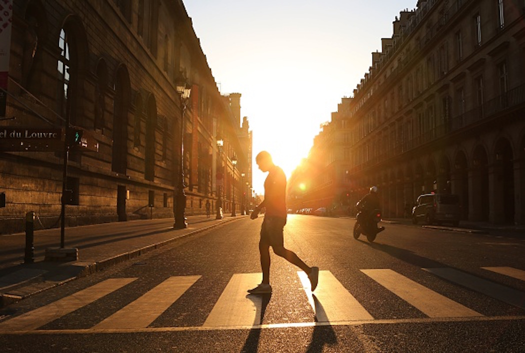 A man walks across the Rivoli street along the Louvre museum at sunset in Paris on June 8, 2015. (Photo by LUDOVIC MARIN/AFP/Getty Images)