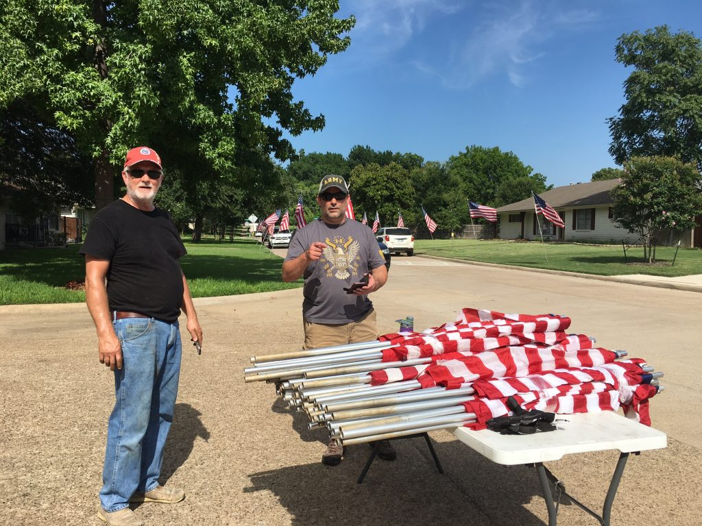 Jerry Reddy and Fred Schmelling prepare American flags for display.