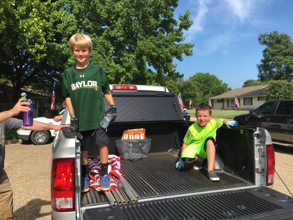 Scouts sweat it out, helping to line Dallas streets with flags.