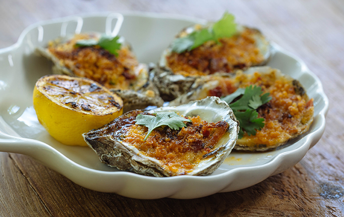 Roasted oysters with bacon, breadcrumbs and red pepper butter. (Photo by Kathy Tran)