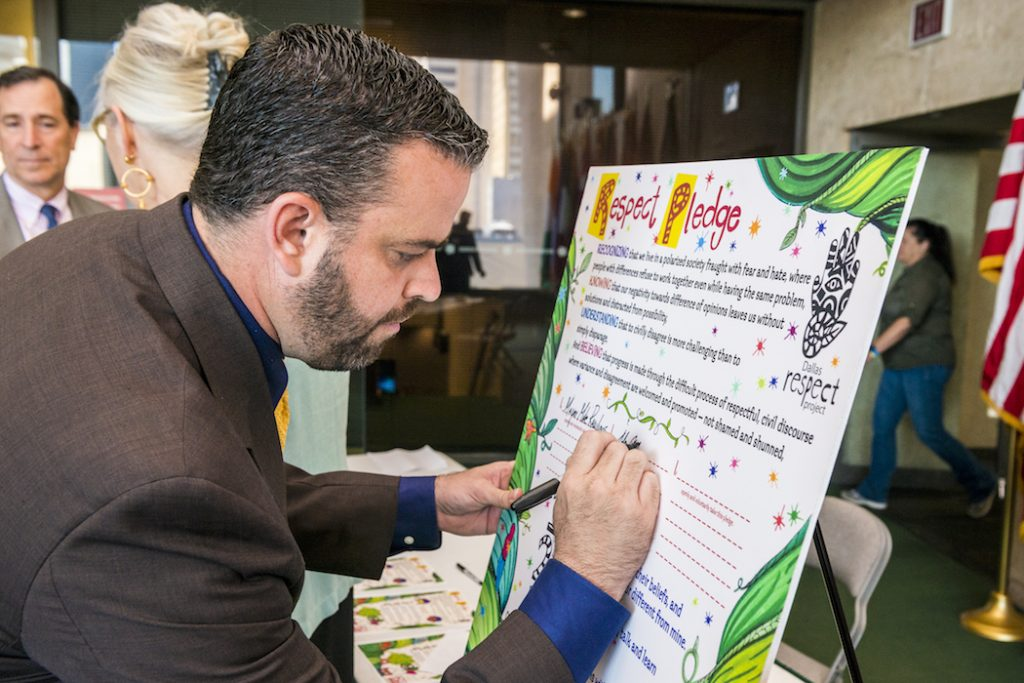 """Councilman Adam McGough signs a """"Respect Pledge"""" during the June kickoff event for the 2016 Dallas Peace Day. Dallas artist and community activist, Karen Blessen, along with young people from 29 Pieces, an inner city arts arts initiative, asked the willing to sign the pledge, committing to respect and peace when beset by adversity. (Photo by Danny Fulgencio)"""