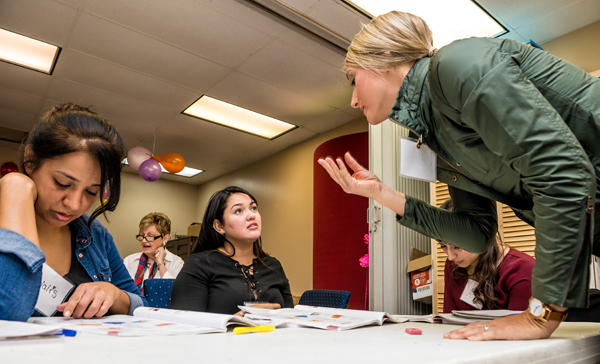 Alejandra Valbuena, middle, and other students learn English from volunteers at Pamper Lake Highlands, a nonprofit benefitting local women and children. She takes adult literacy classes three days a week and recently began working at the charity's childcare center. Photo by Danny Fulgencio